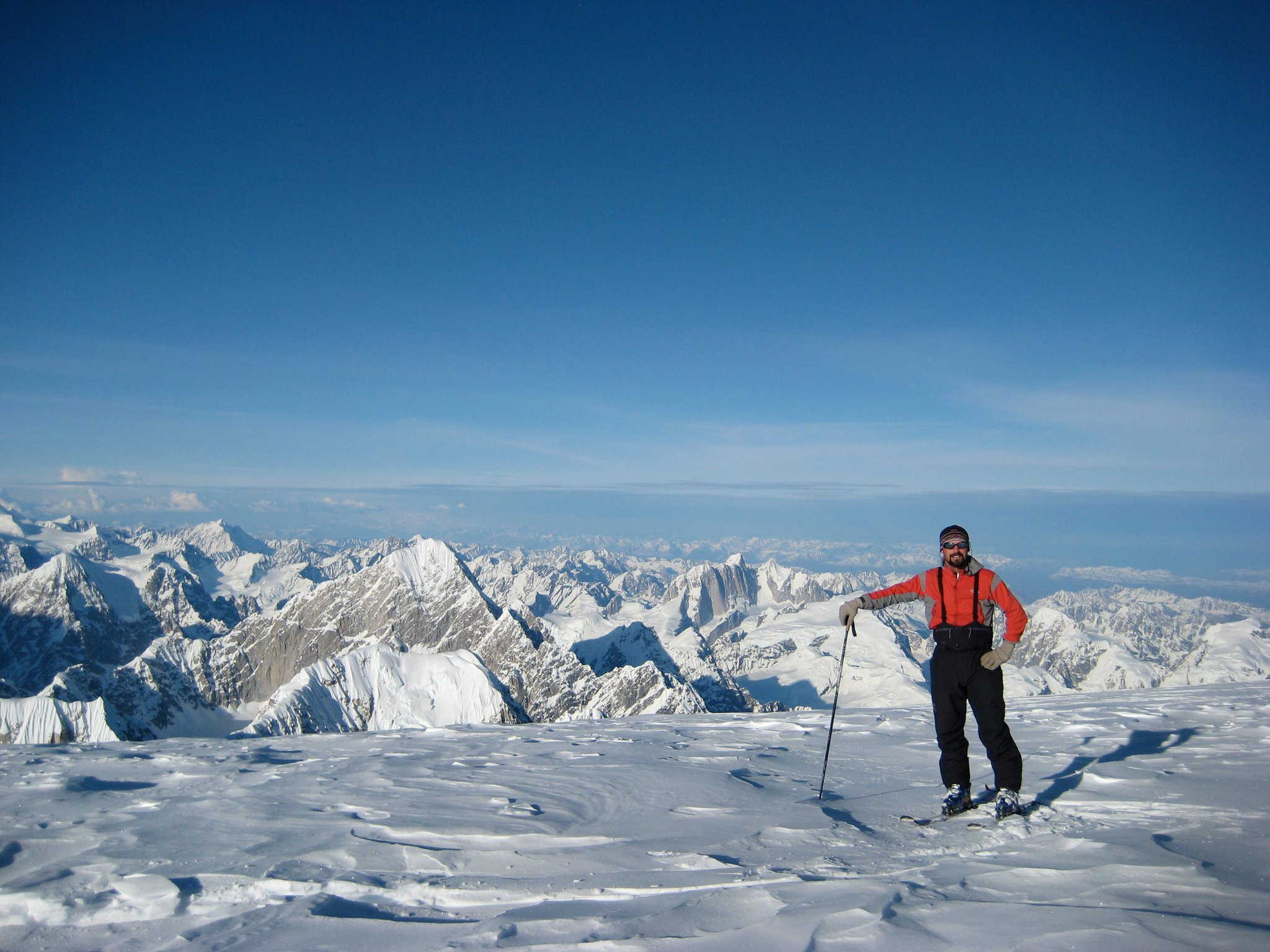 Standing on a saddle of Mount Hunter, Alaska looking towards Mount Huntington (largest peak in the background) and Mooses Tooth in the distance